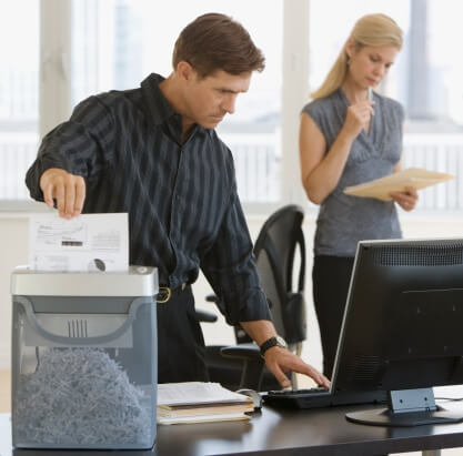 Office worker working on computer while shredding documents in an office shredder